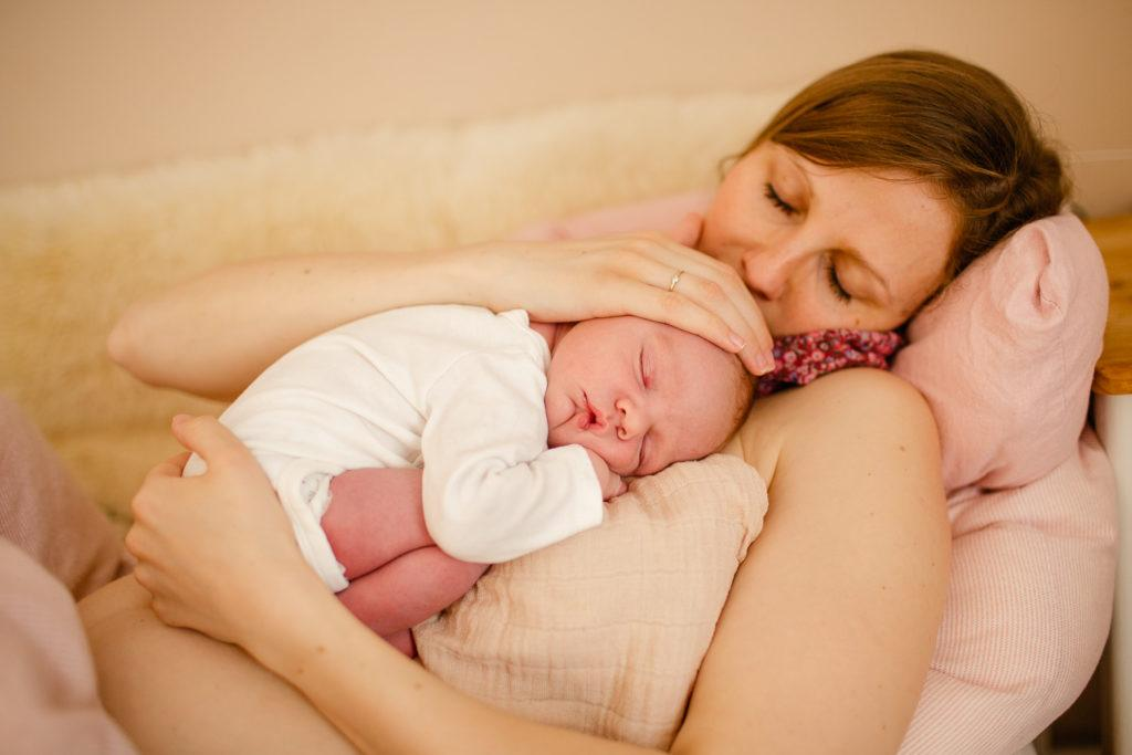 Neugeborenenbilder Baby kuschelt auf Mamas Brust im Bett